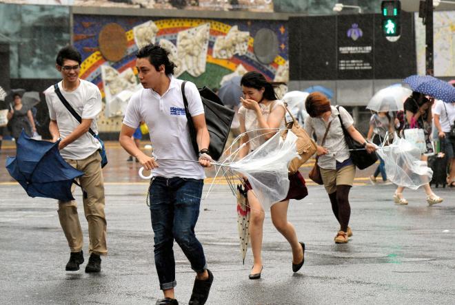台風18号による強風で傘をあおられながら、横断歩道を渡る人たち=2013年9月16日、東京都渋谷区