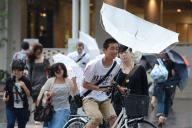 傘が裏返るほどの強風の中、行き交う人たち=2012年6月19日、大阪市阿倍野区