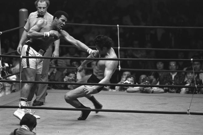 「世紀の凡戦」と揶揄された、モハメド・アリ(左)との異種格闘技戦。試合中、一方が寝て一方が立っている状態を指す、「猪木―アリ状態」という用語が後に定着=1976年6月26日