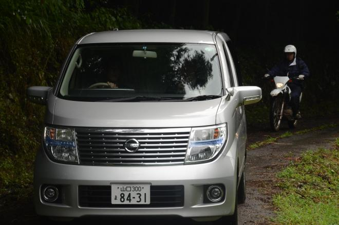 容疑者を乗せているとみられる車と警護する県警のオフロードバイク