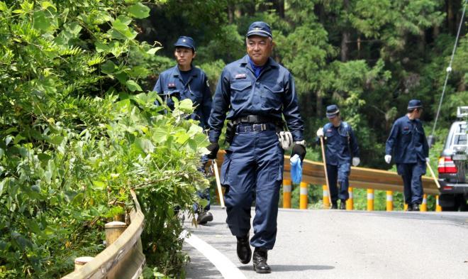 連日、現場付近を捜索する警察官=2013年7月25日午前11時19分、山口県周南市金峰