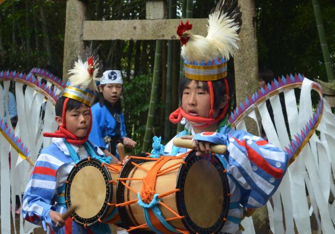 【山口・闘鶏踊り】太鼓をたたき、鶏の剝製(はくせい)と羽根を模した飾りを着けて踊る中学生=2014年4月30日、山口市阿知須