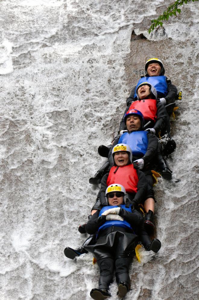 滝を滑り降りる参加者=愛媛県の滑床渓谷
