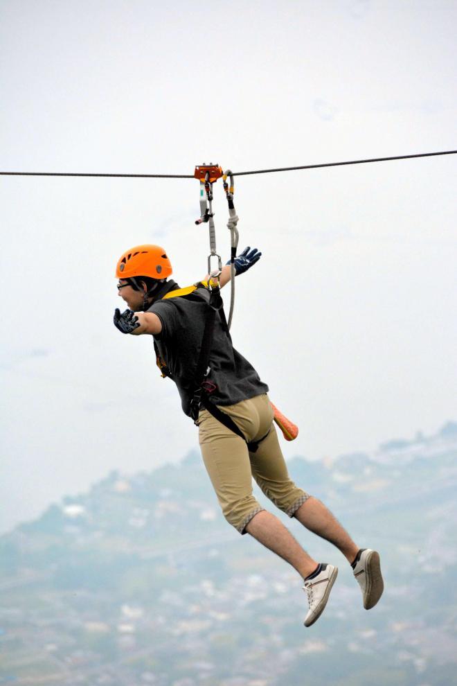 琵琶湖をバックに空中散歩を楽しむ参加者=大津市木戸のびわ湖バレイ