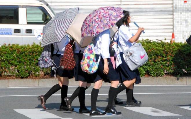 日傘をさして歩く女子高生=2012年6月14日、奈良市
