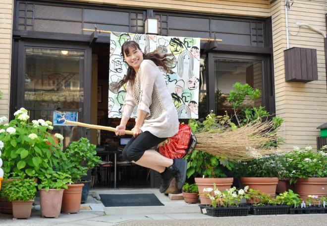 五福通りにあるカフェの前でホウキに乗って主人公を体感する女性=岡山市東区西大寺中