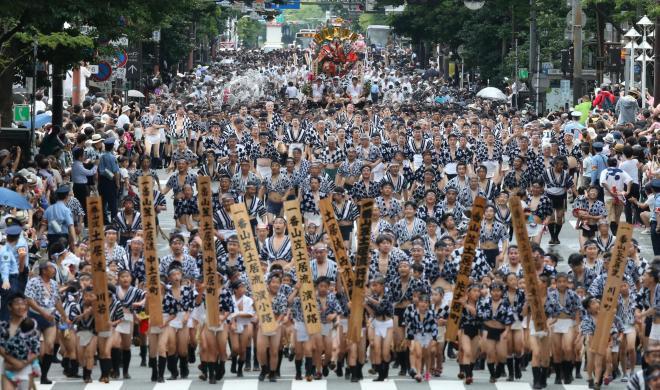 勢(きお)い水を浴びながら通りを駆け抜ける男たち=13日午後、福岡市博多区、藤脇正真撮影
