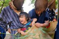 【鹿児島・ヨッカブイ】大泣きする子どもをかますに入れる大ガラッパたち=2013年8月22日、南さつま市