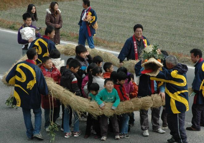 【兵庫・蛇供養】稲わらで編んだ「大蛇」に巻かれる子どもたち=2010年1月11日、南あわじ市倭文安住寺