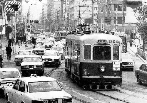 現在の明治通りを走る路面電車。左には県庁前のバス停が見える=1970年12月30日、福岡市