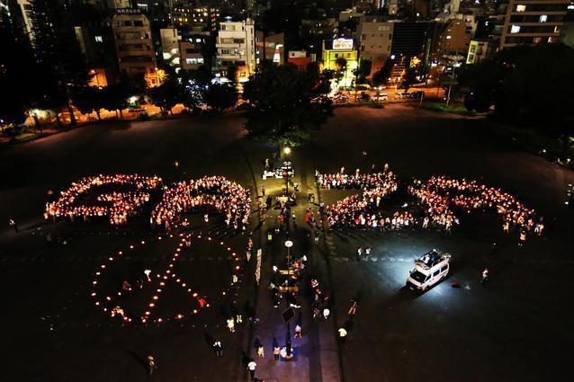 ろうそくをともしガザ地区の和平を訴えるメッセージを掲げる人たち=21日午後7時37分、東京都新宿区の明治公園、遠藤啓生撮影