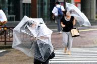 JR鹿児島中央駅前では横殴りの雨と強風の中、ゆがんだ傘を手に歩く姿が見られた=10日午前9時、鹿児島市、上田幸一撮影