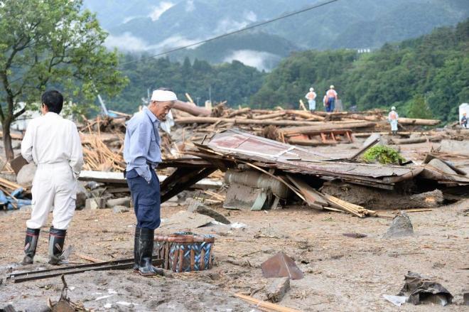 土石流の被害現場を心配そうに見つめる住民たち=10日午前6時27分、長野県南木曽町、白井伸洋撮影