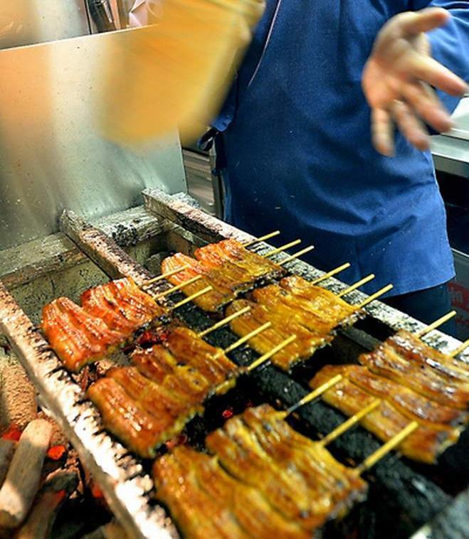 蒸したウナギを焼き上げる職人