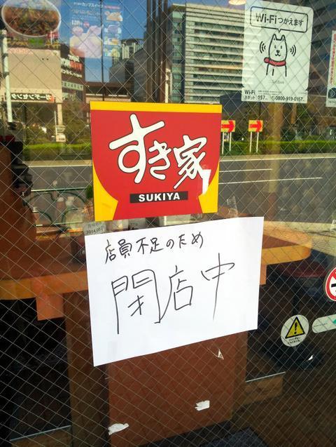 「店員不足のため閉店中」と掲げる店舗=4月上旬、都内の「すき家」
