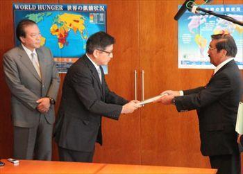 第三者委の久保利英明委員長が調査報告書を提出。ゼンショーホールディングスの小川賢太郎社長(左)、ゼンショーの興津龍太郎社長(真ん中)が受け取った=東京都港区のゼンショーHD。同社提供