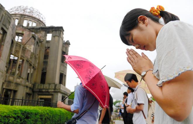 原爆ドームの前で手を合わせ、黙禱(もくとう)をする女性=6日午前8時15分、広島市中区、遠藤真梨撮影