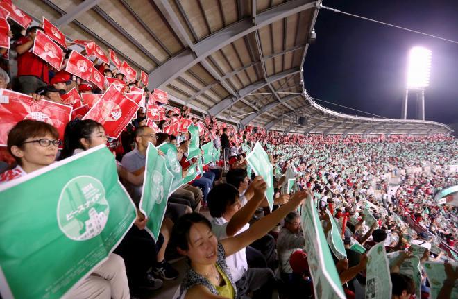 曲に合わせて緑や赤の紙を振る観客ら=30日夜、広島市南区、青山芳久撮影