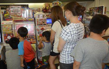 妖怪メダルを使って遊べるゲーム機の前に親子らが列をなしていた=2014年7月31日、東京都中央区の博品館トイパーク銀座本店
