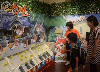 妖怪ウォッチのイベントショップ「妖怪タウン」のゲームで遊ぶ親子=2014年8月1日、東京都江東区のダイバーシティ東京プラザ
