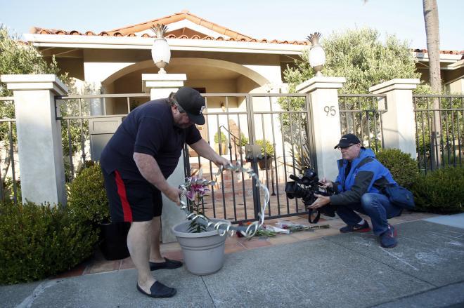 ロビン・ウィリアムズさんの自宅前に花を置くファン