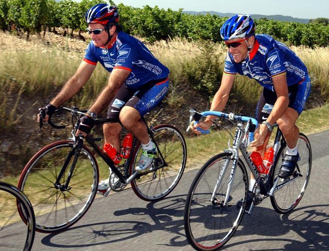 ツール・ド・フランスで、大好きな自転車に乗るロビン・ウィリアムズ氏(左)。2002年7月
