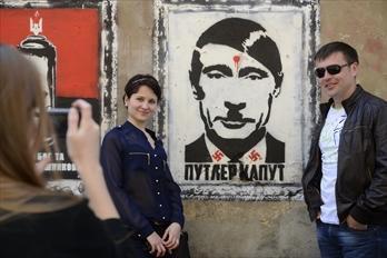 ウクライナのプーチン大統領を批判するポスター。襟には鍵十字。その前で笑顔で記念写真を撮る人=2014年5月