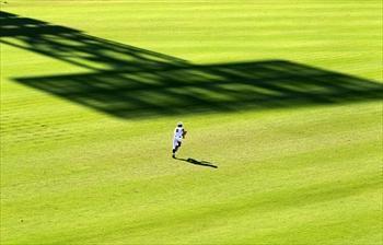 照明塔の影が伸びる芝生は強烈な西日で照り輝いていた=2010年8月8日、矢木隆晴撮影