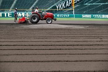 グラウンドの土の「こりをとる」ため、土を掘り起こす作業をする甲子園球場のグラウンドキーパー=2014年7月11日、兵庫県西宮市、橋本弦撮影
