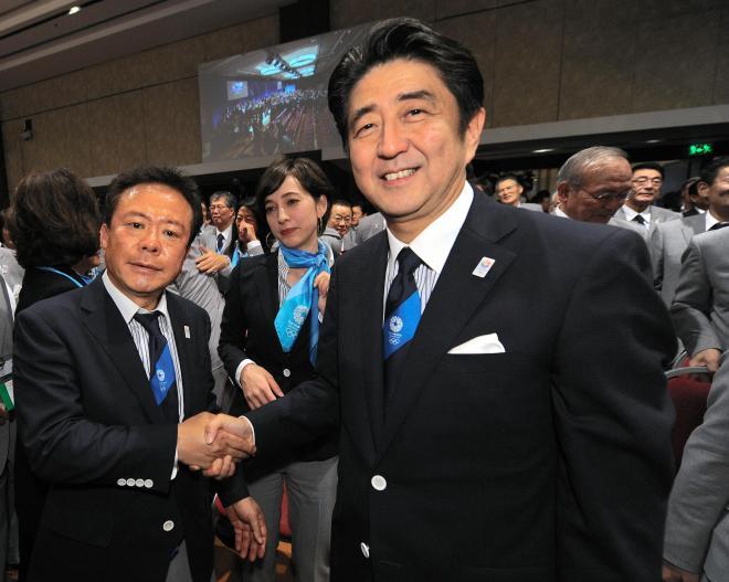東京での五輪開催決定を受け、ガッチリ握手をかわす安倍首相と猪瀬直樹氏=2013年9月7日、ブエノスアイレス