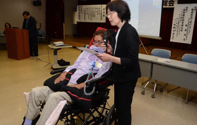 ALS患者の岡本充雄さん。用意した文章を妻典子さんが代読し、「患者のみなさん、生きて生きて生き抜こうではありませんか」と呼びかけた=2014年5月24日、東京都新宿区、村井七緒子撮影