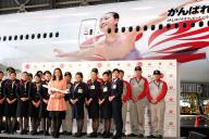 自身の姿が描かれた航空機の前で、客室乗務員らと並ぶ浅田真央選手(左中央)=2013年12月25日、東京都大田区