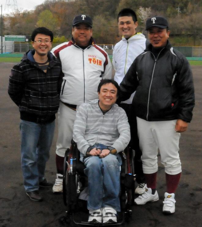 大阪桐蔭の同級生と車いすで母校のグラウンドを訪れた、平岡成浩さん(中央)を迎える、西谷浩一監督(左から2番目)ら=2013年4月7日