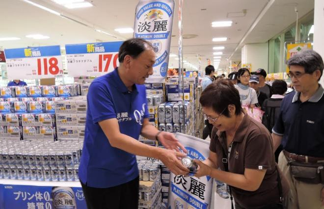 キリンビールマーケティングの布施孝之社長が頭を下げ、行列客に一人ずつサンプルを手渡した