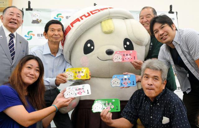 さのまるのナンバープレート「1番」を抽選で手にした人たち=栃木県佐野市東仮庁舎議場棟