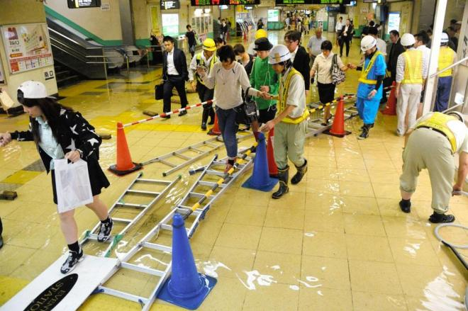 JR新小岩駅。足元が水にぬれないよう、急きょハシゴを敷いて「道」をつくった=10日午後9時29分、東京都葛飾区、白井伸洋撮影