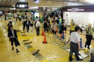 水浸しになったJR新小岩駅の通路を歩く乗客ら=10日午後9時29分、東京都葛飾区、白井伸洋撮影