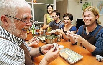 巻きずし作りを体験する米国人観光客たち=京都府亀岡市千歳町