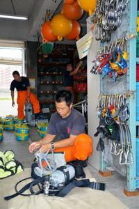 救助に使う空気ボンベなどの機材を点検する特殊救難隊員たち=東京都大田区羽田空港1丁目