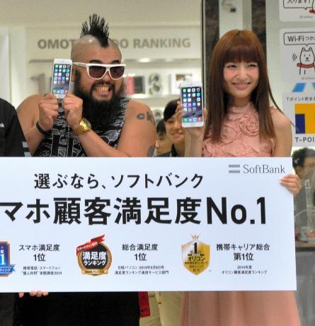 ソフトバンクの表参道の販売店で、最初にiPhone6を手にした男性(左)と記念撮影に応じるゲストの神田沙也加さん=9月19日午前8時すぎ、東京都渋谷区