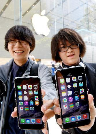iPhone6(左)とiPhone6プラスを手に笑顔を見せる男性=9月19日午前9時24分、東京都渋谷区、日吉健吾撮影
