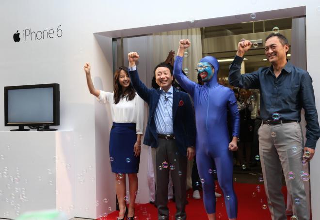 iPhone6の販売開始式典に参加した(左から)堀北真希さん、加藤薫NTTドコモ社長、一番乗りした男性、渡辺謙さん=9月19日、東京・有楽町、山口明夏撮影