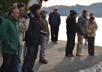 猪鼻湖底で人工物が発見されたと聞き、ダイバーを見守るスマッペのメンバーや地元住民ら=2013年1月6日、浜松市北区三ケ日町