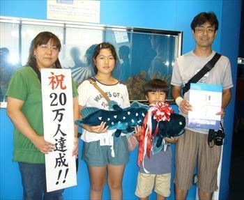 20万人目の入館者となった鈴木さん一家に記念品が贈られた=2012年9月1日、沼津市千本港町
