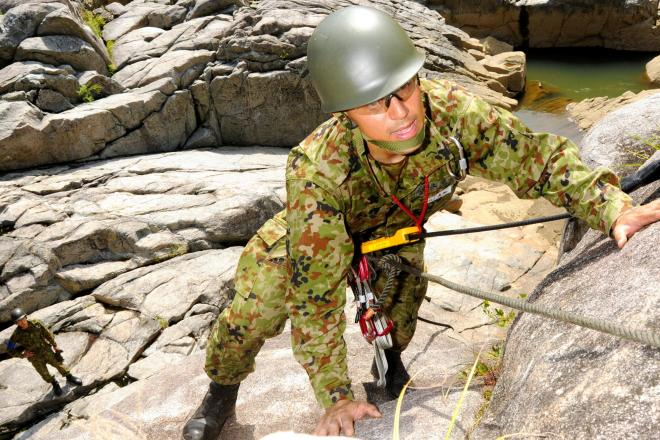 岩の壁を登る隊員=26日、福島市飯野町明治。小島泰生撮影