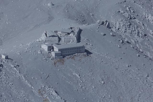 噴煙を上げる御岳山火口付近の山小屋は、火山灰に覆われた=27日午後2時18分、朝日新聞社ヘリから、池永牧子撮影