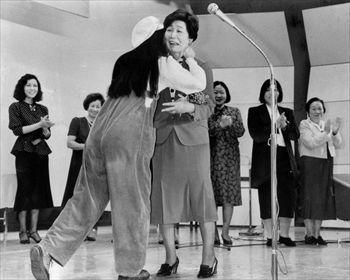 土井委員長を励ます女性の政治集会「いま始まります。女の政治」で作家の森村桂さんに抱きつかれ、激励を受ける土井たか子社会党委員長(中央)=1986年10月8日