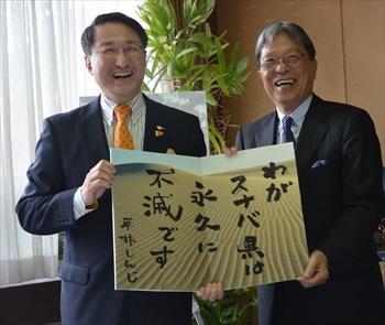 スターバックスコーヒーの出店を受け、鳥取県の平井伸治知事が考えた言葉「わがスナバ県は永久に不滅です」が書かれたパネルを持つスターバックスコーヒーの関根純・最高経営責任者(右)と平井知事=2014年9月12日