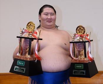 殊勲賞と敢闘賞のトロフィーを手に笑顔を見せる逸ノ城=白井伸洋撮影