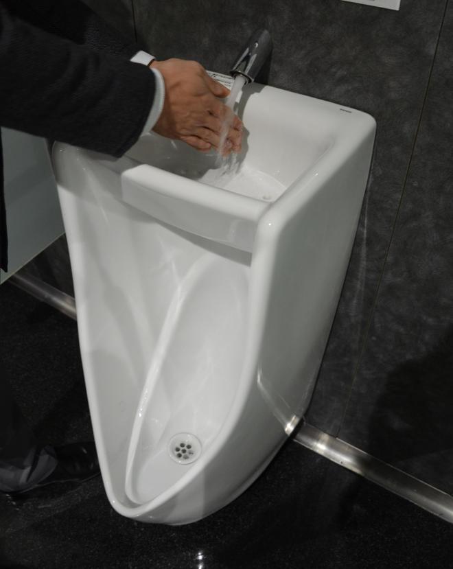 「手洗い器つき小便器」で手を洗う。器の高さがひじより下にあるため、洗いやすい。水は下の小便器の洗浄に回り、トータルで節水する仕組みだ=大津市